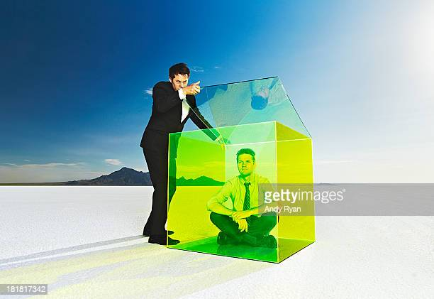 Businessman shutting the lid on man in a box.