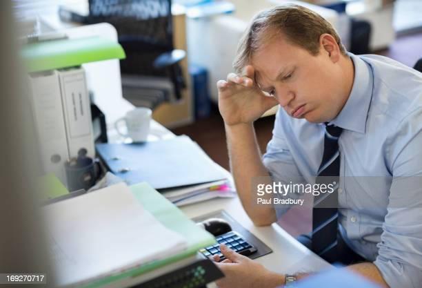 Businessman sighing at desk
