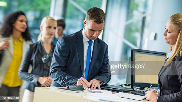 Businessman signing a document at a bank counter