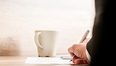 Businessman signing a document or contract with a mug of coffee standing on the desk, low angle view between his arm of the paperwork.