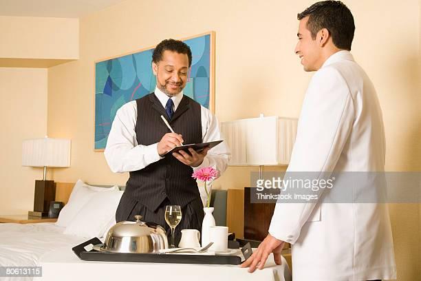 Businessman signing bill for room service