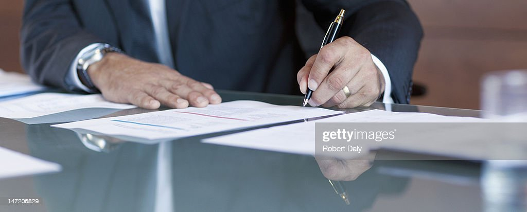 Businessman signing contract at table : Stock Photo