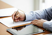Businessman signing documents on desk in office