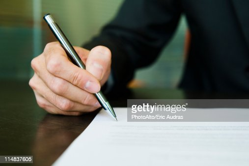 Businessman signing paperwork, cropped : Stock Photo