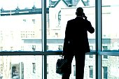 Businessman silhouetted in large office window.