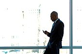 Businessman silhouetted in large office window, using PDA smart phone.
