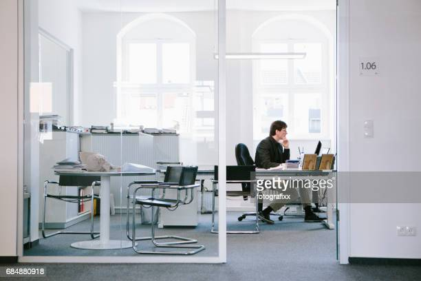 businessman sit alone at desk in office, looking in monitor