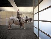 A Businessman Sits Astride A Rhinoceros In An Offi