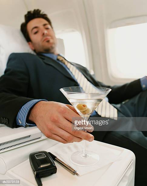 Businessman Sits in a Plane Holding a Martini, Focus on the Foreground