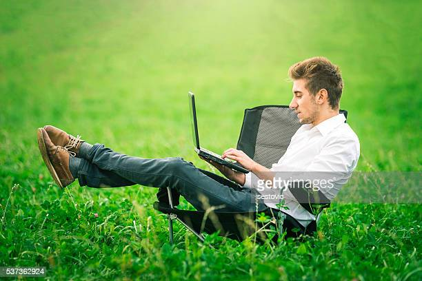 Businessman sits in an office chair in a field