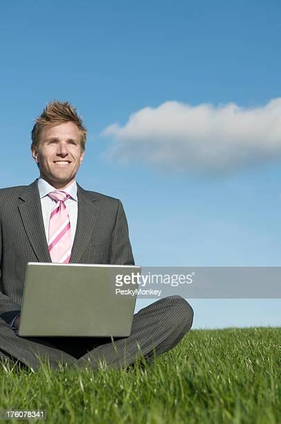 Geschäftsmann sitzt in Wiese mit Laptop