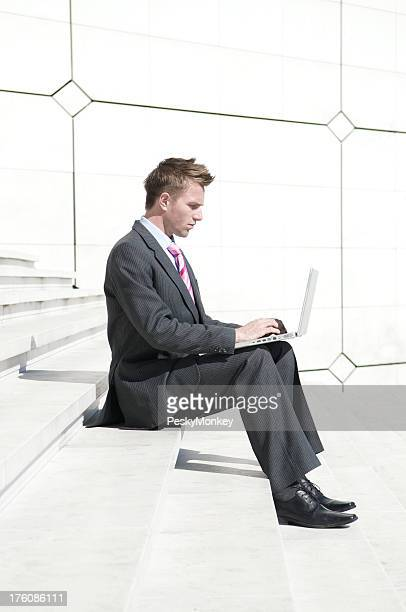 Businessman Sits Typing on White Steps