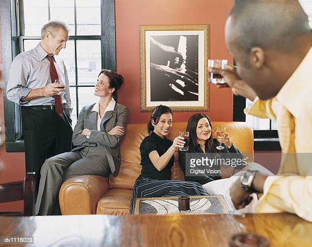 Businessman Sitting at a Bar Acknowledging Businesswomen with His Drink