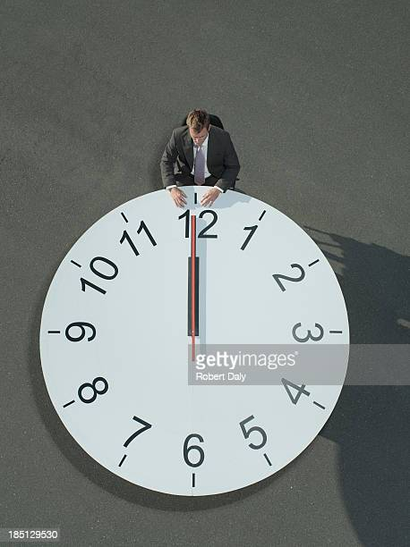 A businessman sitting at a clock table