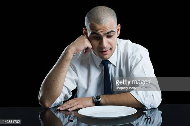 Businessman sitting at a dining table and thinking