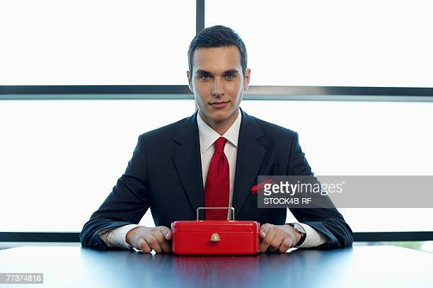 Businessman sitting at a table with a cash box
