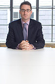 Businessman sitting at a table with his hands clasped in an office