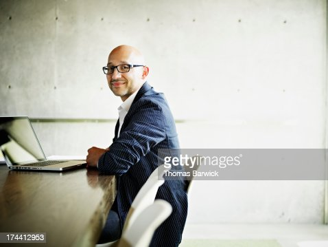 Businessman sitting at conference room table : Stock Photo