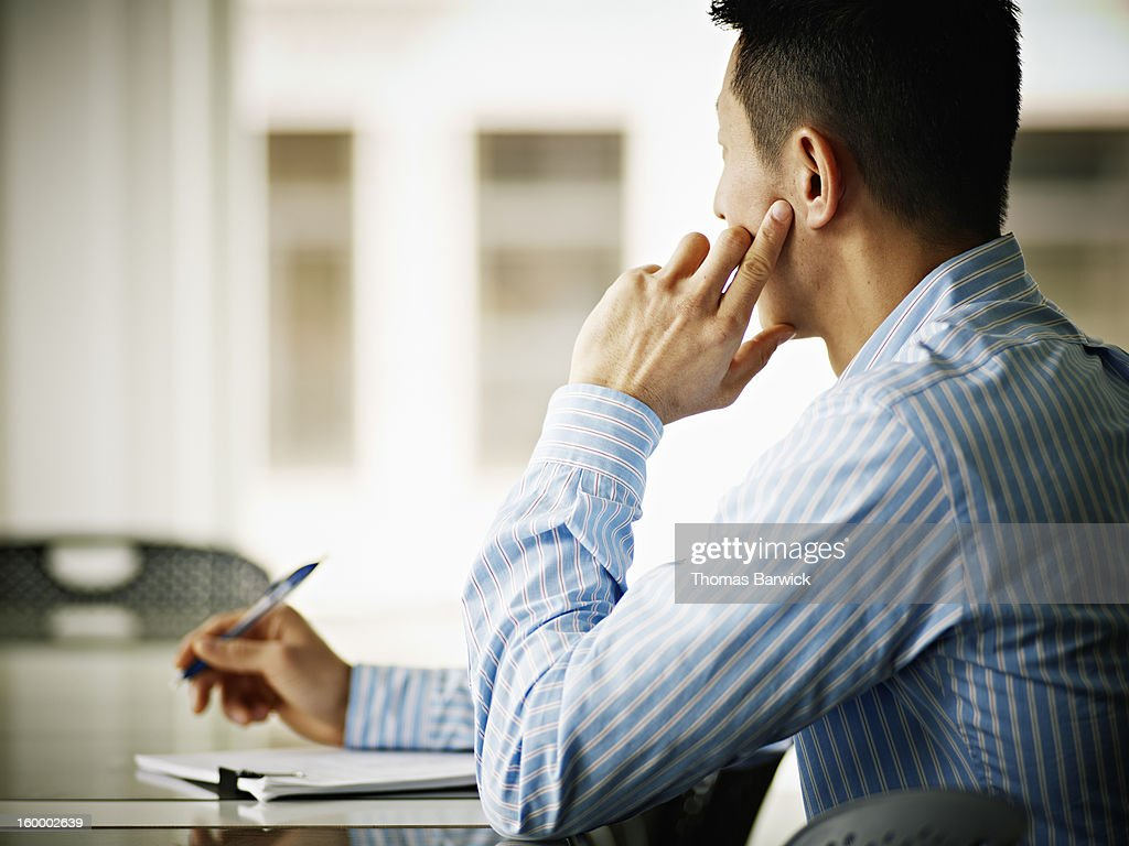 Businessman sitting at conference table : Stock Photo