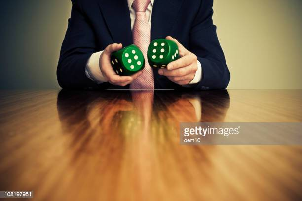Businessman Sitting at Desk and Holding Pair of Dice