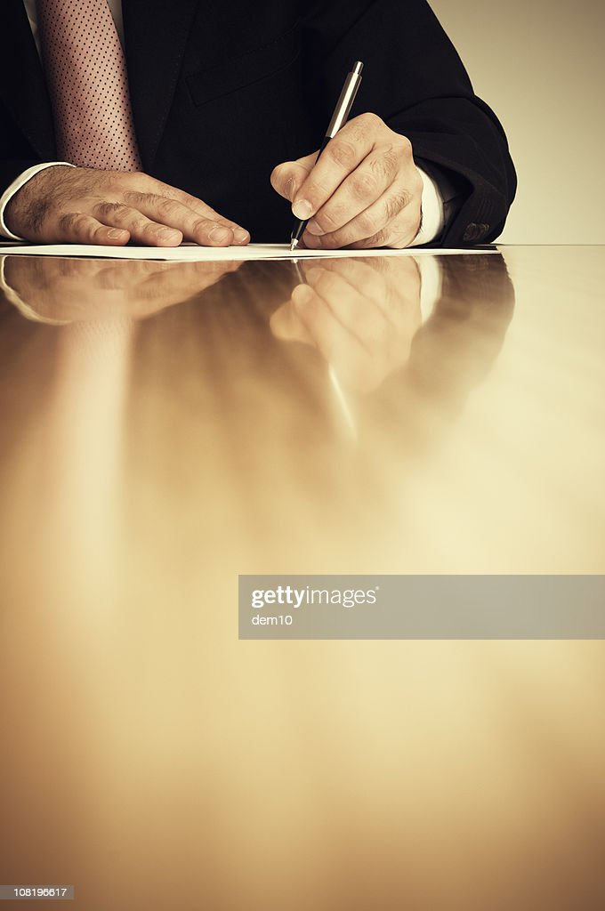 Businessman Sitting at Desk and Writing on Paper : Stock Photo