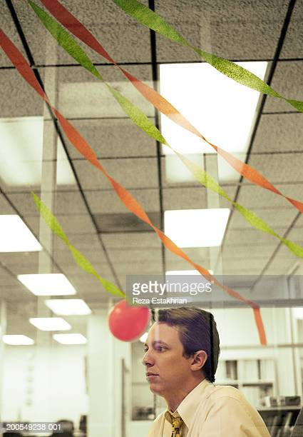 Businessman sitting at desk, balloons and streamers in background