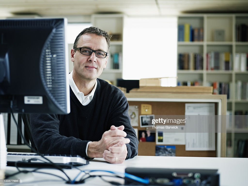 Businessman sitting at desk behind computer : Stock Photo