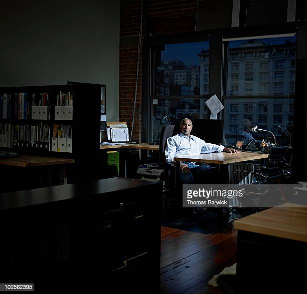 Businessman sitting at desk in empty office