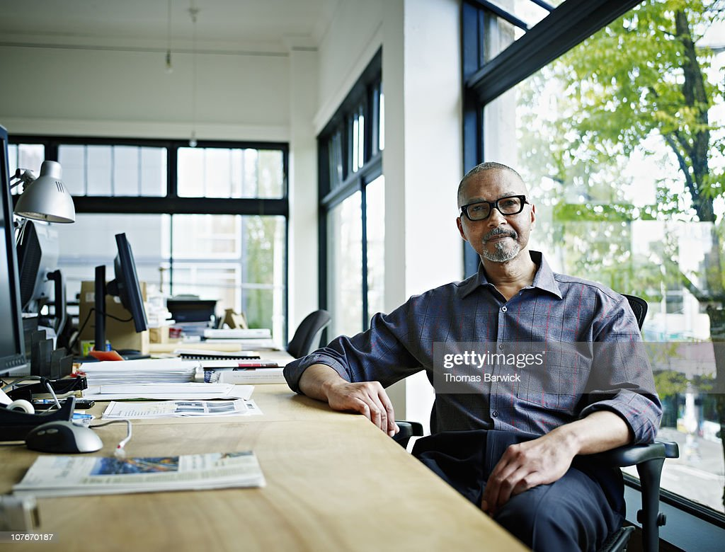 Businessman sitting at desk in office : Stock Photo