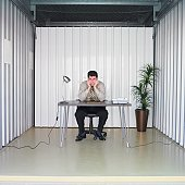 Businessman sitting at desk in storage unit