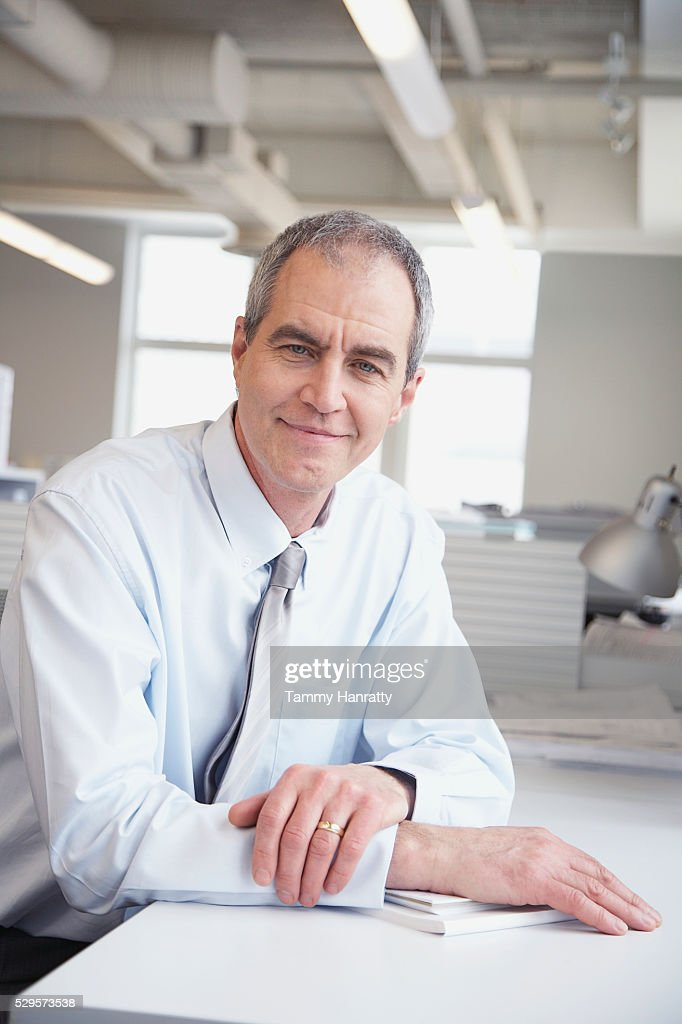 Businessman sitting at desk : Stock Photo