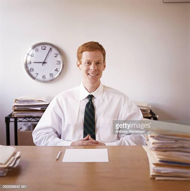 Businessman sitting at desk, portrait