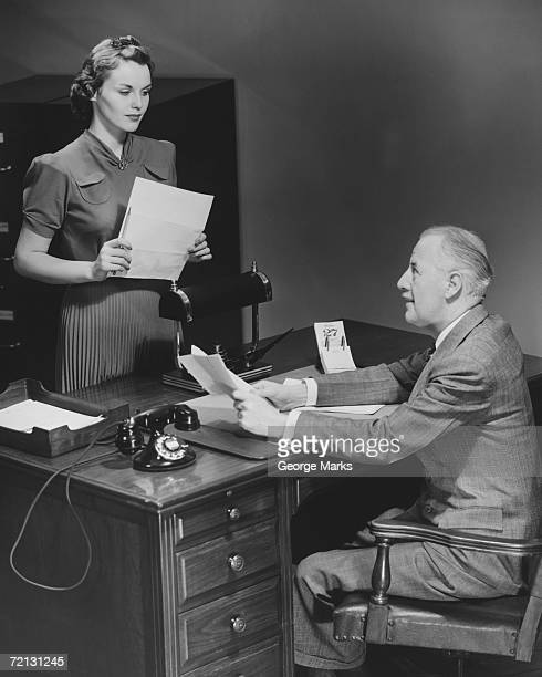 Businessman sitting at desk talking to secretary (B&W)