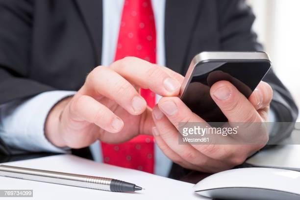 Businessman sitting at desk text messaging, close-up