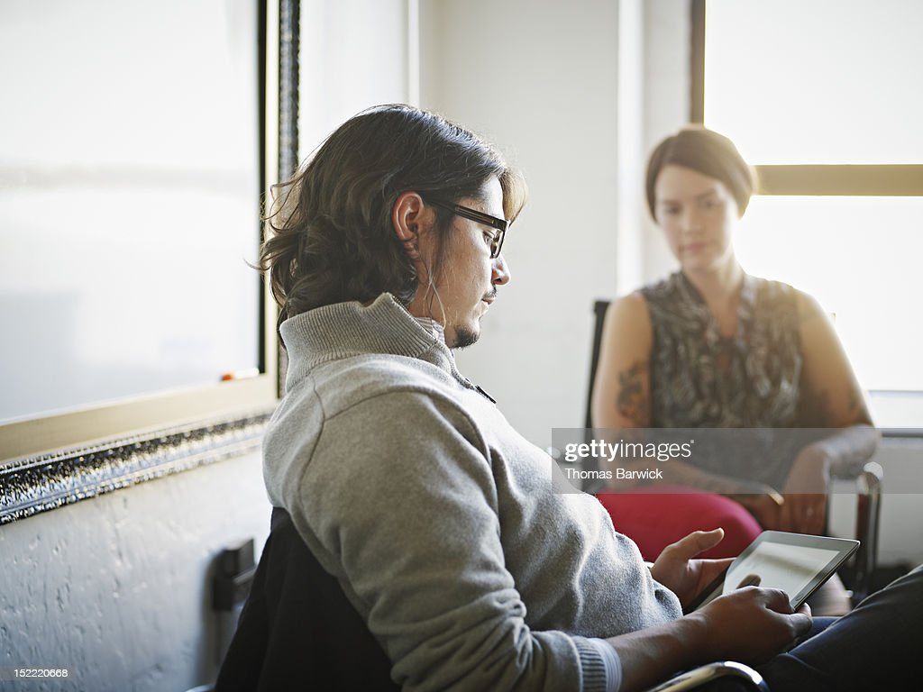 Businessman sitting at desk using digital tablet : Stock Photo