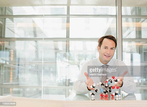 Geschäftsmann, sitzen am Schreibtisch mit Molekül-Modell