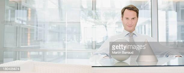 Businessman sitting at desk with sculptures