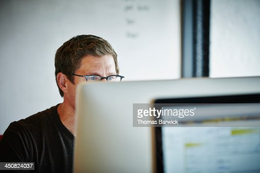 Businessman sitting at desk working on computer