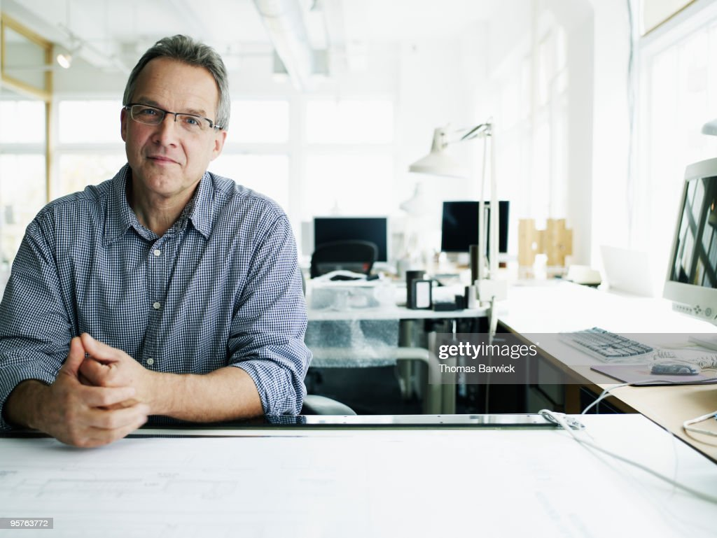 Businessman sitting at drafting table in office : Stock Photo