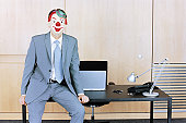 Businessman sitting at edge of desk wearing clown mask