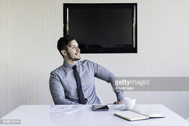 Businessman sitting at his desk smiling.
