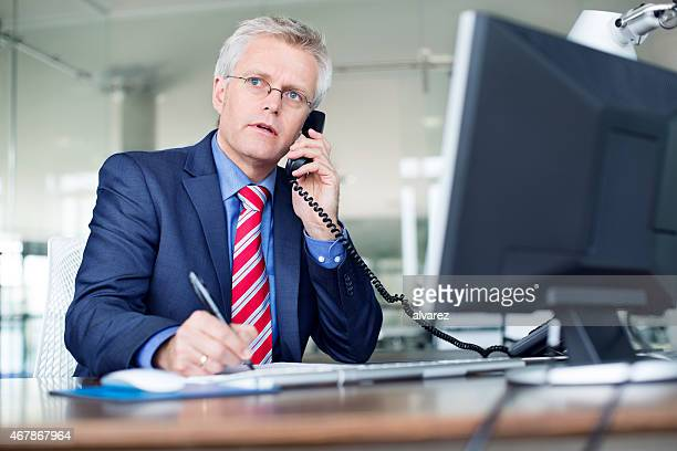 Businessman sitting at his desk talking on telephone
