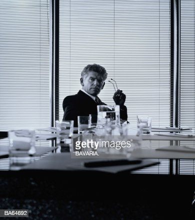 Businessman sitting at table in boardroom, portrait (B&W) : Stock Photo
