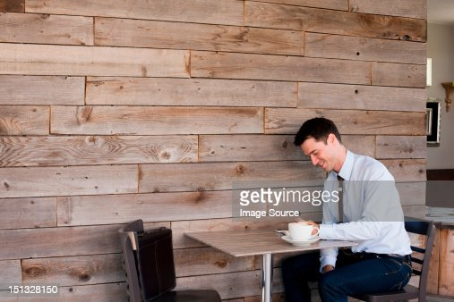 Businessman sitting at table in cafe : Stock Photo