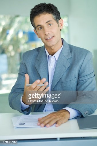 Businessman sitting at table with document, holding pen and gesturing : Stock Photo