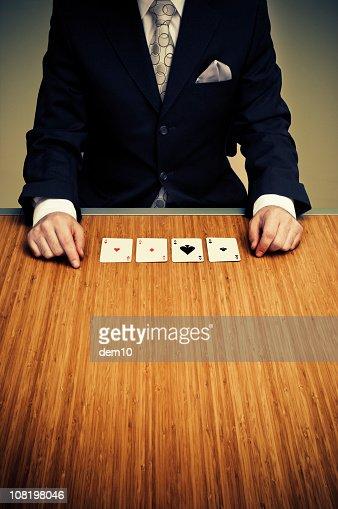 テーブルに座っているビジネスマン、4 つのエースカード