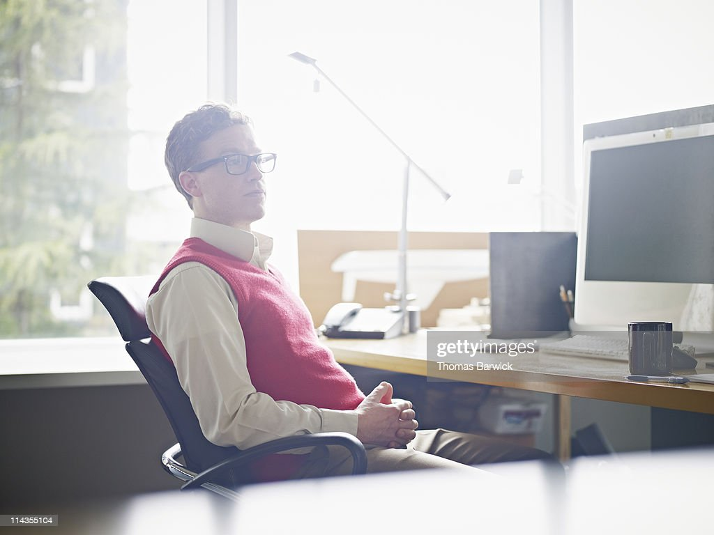 Businessman sitting at workstation in office : Stock Photo