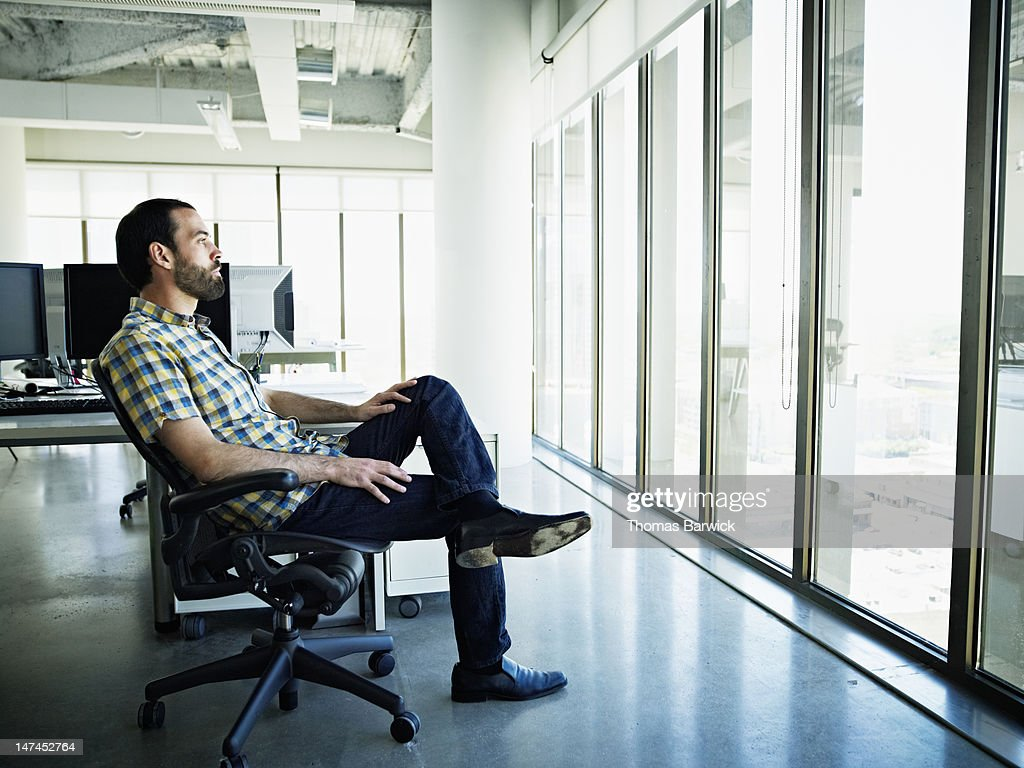 Businessman sitting at workstation looking out : Stock Photo