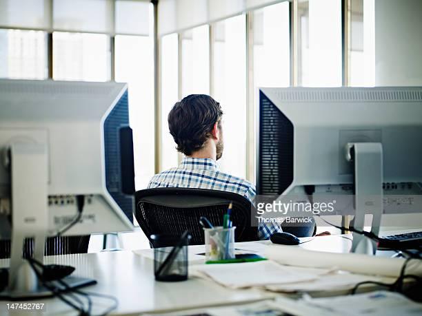 Businessman sitting at workstation rear view
