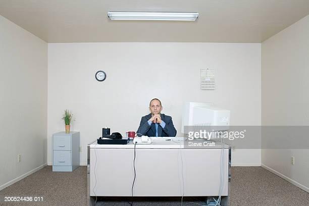 Businessman sitting behind desk, portrait